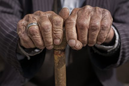 Old aged pensioner holding a cane in between his hands