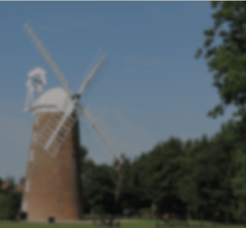Windmill in Dereham surrounded by trees against a blue skyline