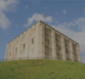 Norwich Castle sitting on top of green hill against blue sky background
