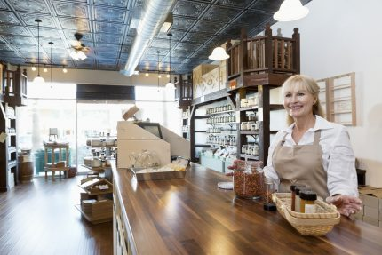 Happy blonde female spice store owner at counter looking into distance