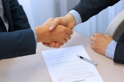 Two young Business professionals shaking hands over the signing of a business contract