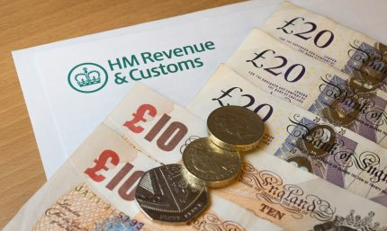 HMRC form on desk with British bank notes and pound coins lined up on top