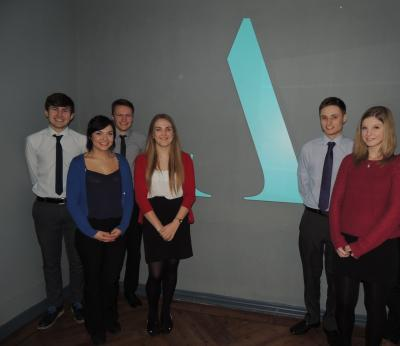 Aston Shaw Apprentices standing in front of company logo