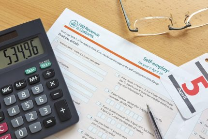 HMRC sheet on desk with calculator sat on top