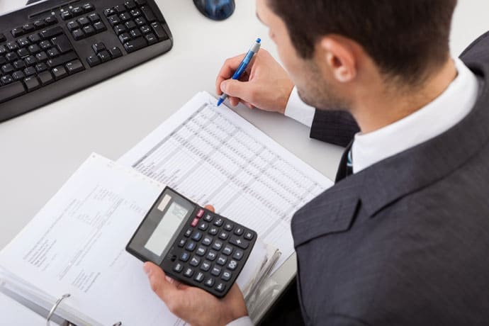 Young accountant holding calculator working out tax returns