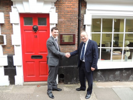Mark Noakes and Roger Hopkins stood in front of building shaking hands after successful business agreement