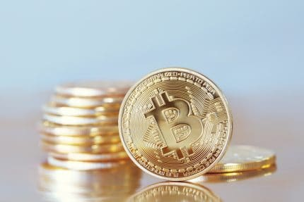 Bitcoin standing up right with other bitcoins piled up in background