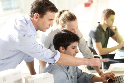 Employees showing an apprentice what to do on a computer