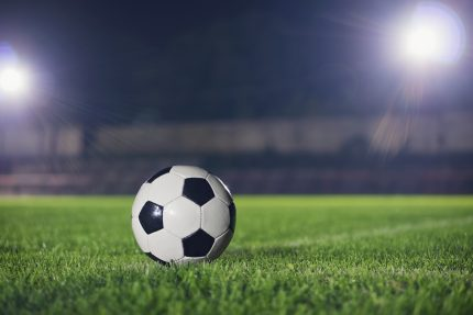 vintage football on grass with floodlights shining down on it