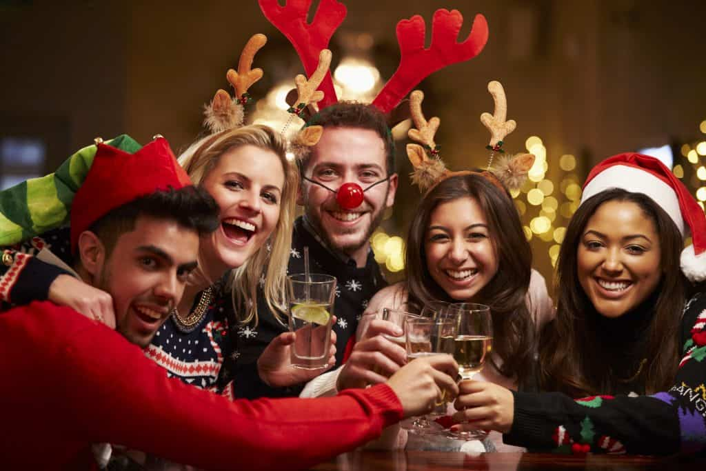 Group of work colleagues smiling with drinks at Company Christmas Party