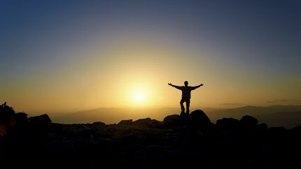 Man with arms outstretched standing on top of mountain with sun setting