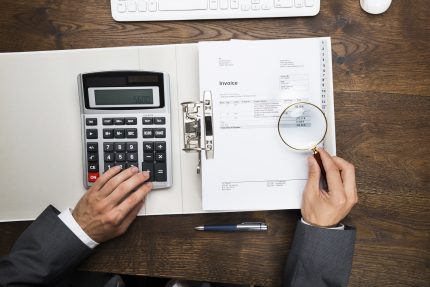 Businessman examining tax invoice through magnifying glass at desk