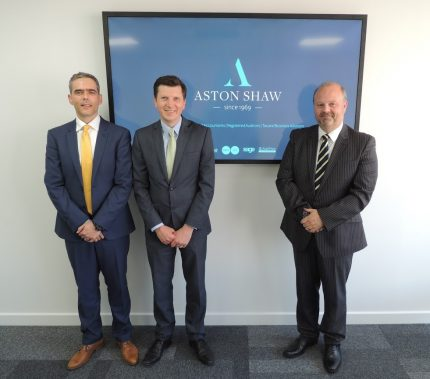 Three Aston Shaw accountants smartly dressed standing in front of a television screen displaying the business logo
