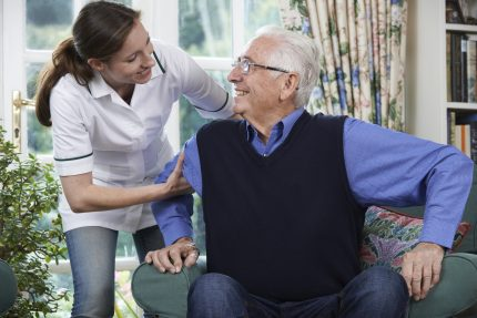 Care Worker Helping Senior Man To Get Up Out Of Chair