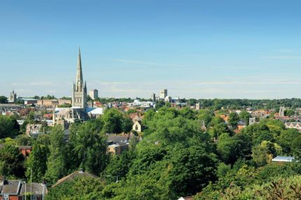 A photo taken from Mousehold Heath on a Summer's day in the city of Norwich. The image shows many landmarks including the Cathedral, The Forum, City Hall and the Roman Catholic Cathedral.