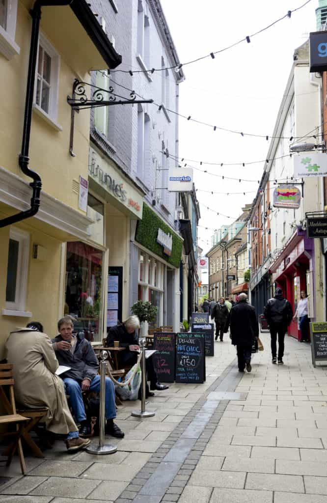 """Norwich, England - May 15, 2012: People enjoying the cafes and shops in Lower Goat Lane, Norwich. The Norwich Lanes are narrow alleyways in the historic quarter of the city, which are lined with small independent shops and quirky cafes. (Overcast day with white sky.)"""