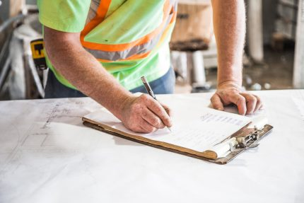 Construction Person Writing on Paper on Top of Table