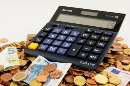 Photo of Calculator Surrounded by Foreign Currency