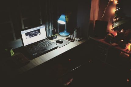 An image showing someone's 'working from home' set-up, including a laptop and several mobile devices.